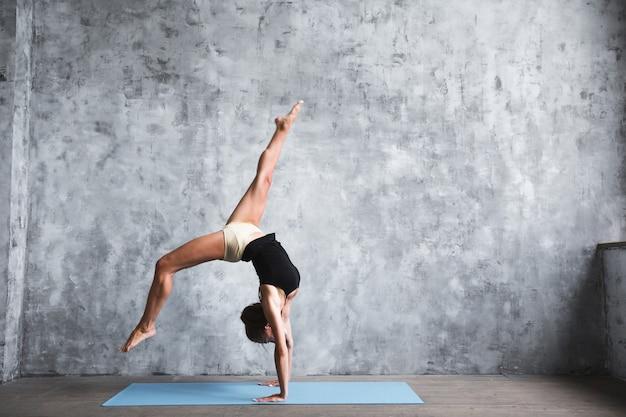 Молодая темноволосая женщина тренируется на фитнес-коврике во время стойки на руках