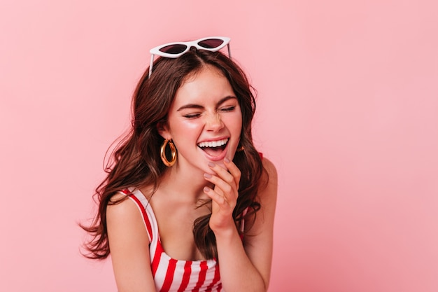 Young dark-haired woman in great mood is laughing with closed eyes on pink wall