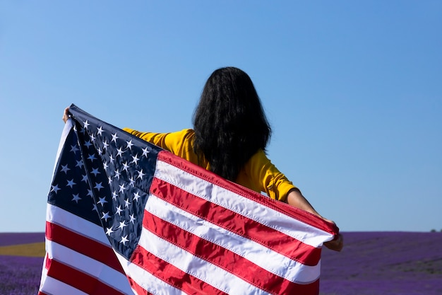 A young, dark-haired woman holding the flag of the united states of america against the sunny sky. memorial day and usa independence day concept.