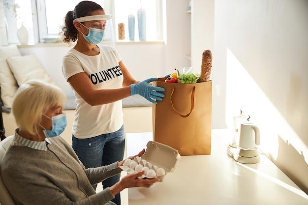 Молодая темноволосая женщина кладет бумажный пакет с едой на стол на кухне