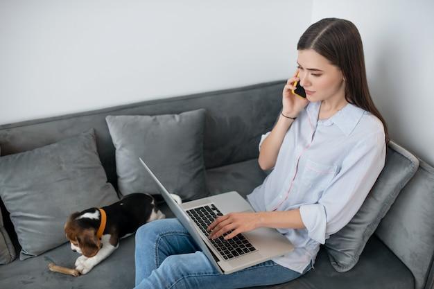 Молодая темноволосая женщина сидит со щенком и разговаривает по телефону