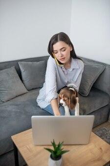 子犬と一緒に座って電話で話している若い黒髪の女性