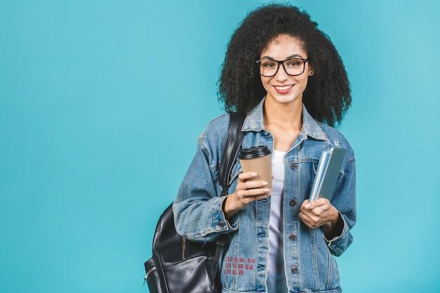 Молодая темнокожая афроамериканка пьет кофе и держит книги и планшетный компьютер