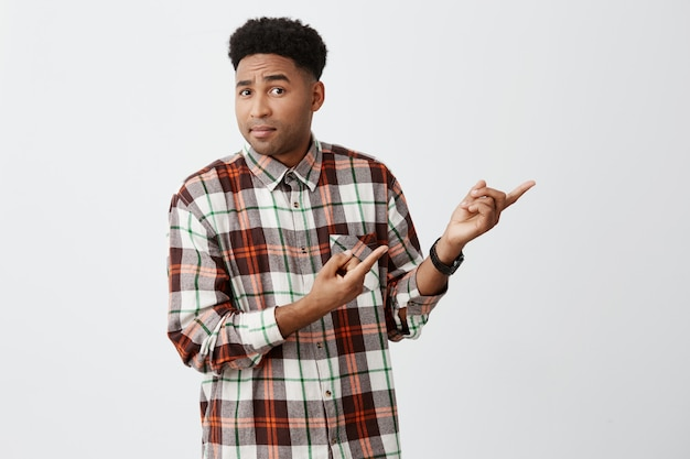 Young dark-skinned african attractive male student with stylish curly hairstyle in casual checkered shirt pointing aside with both hands with confused and questioning expression