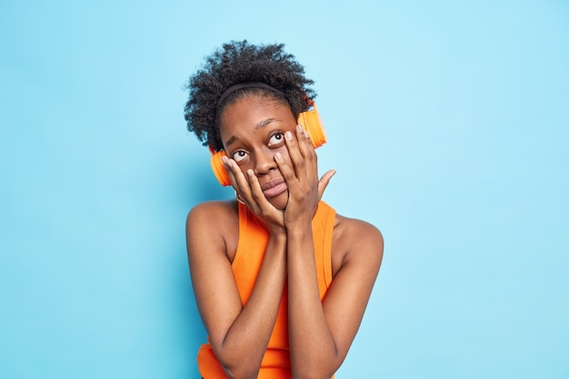 검은 피부의 곱슬머리 아프리카계 미국인 여성은 지루함을 느끼며 얼굴에 손을 대고 헤드폰을 통해 음악을 듣습니다.