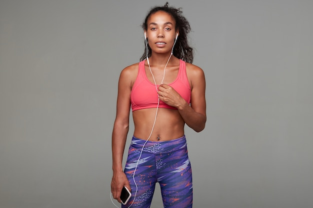 Young dark skinned curly long haired brunette female woman lady with ponytail casual hairstyle dressed in wearing sporty athletic pink wear top clothes standing posing isolated