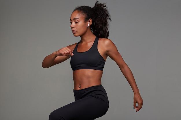 Giovane donna riccia dalla pelle scura in buona forma fisica che ascolta la musica con gli auricolari e si allena mentre posa in abbigliamento sportivo