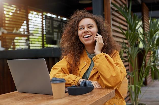 Молодая темнокожая кудрявая женщина сидит на террасе кафе, работает за ноутбуком, пьет кофе, смеется и разговаривает по телефону с другом. в желтом пальто.