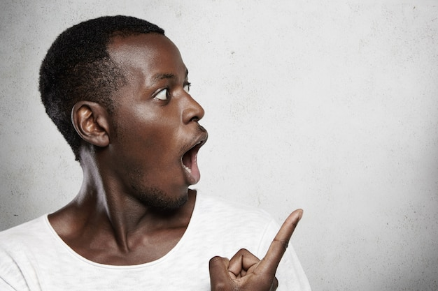Young dark-skinned customer or employee looking in shock, opening mouth widely, showing something surprising pointing at white blank wall
