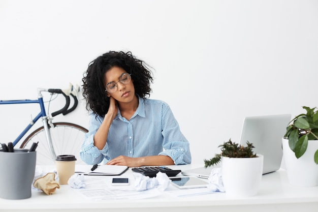 Young dark-skinned freelancer accountant almost sleeping after managing annual financial