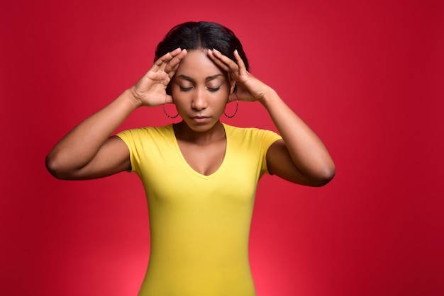 Young dark-skinned girl in a yellow t-shirt has a headache and holds her head in her hands.