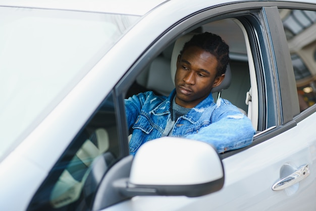 A young dark-skinned man sitting in a car in a white t-shirt