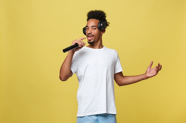 Young dark-skinned man with afro haircut in white t shirt, gesticulating with hands
