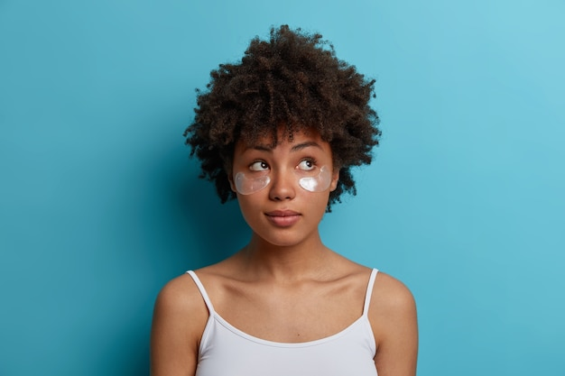 Young dark skinned woman with afro hair applies hydrogel silver patches under eyes, reduces puffiness, removes dark circles. skin care concept
