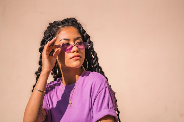 A young dark-skinned woman with purple glasses in an urban session of latin ethnicity, looking to the right