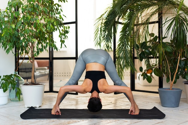 Young darkhair woman practicing yoga in the morning at her home near plants. the woman is engaged in self-determination, doing yoga exercises.
