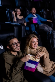 Young dates with box of popcorn sitting in dark cinema and looking at large screen while watching movie at leisure