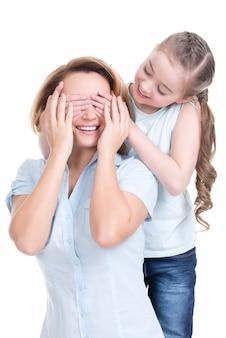 Молодая дочь закрывает руки глаза маме - изолированные