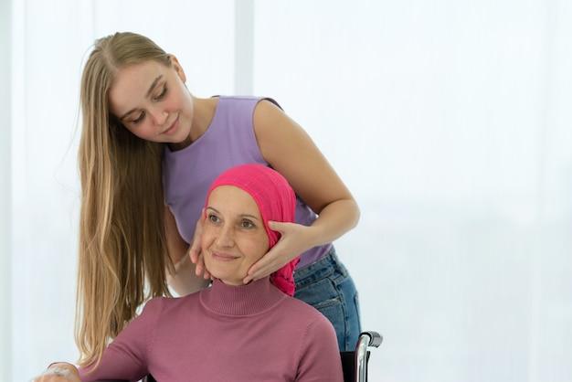 Молодая дочь обнимает свою больную маму, которая в платке на инвалидной коляске