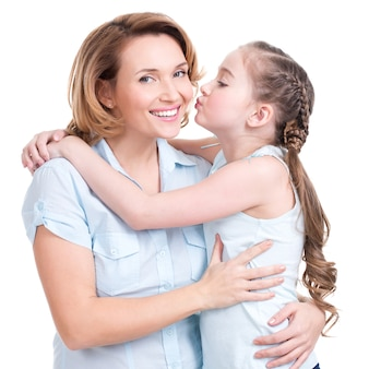 Молодая дочь, целуя мать - изолированные