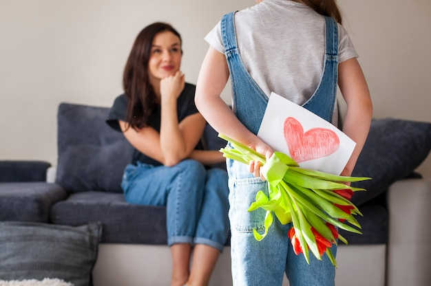 Young daughter surprising mother with flowers and drawing
