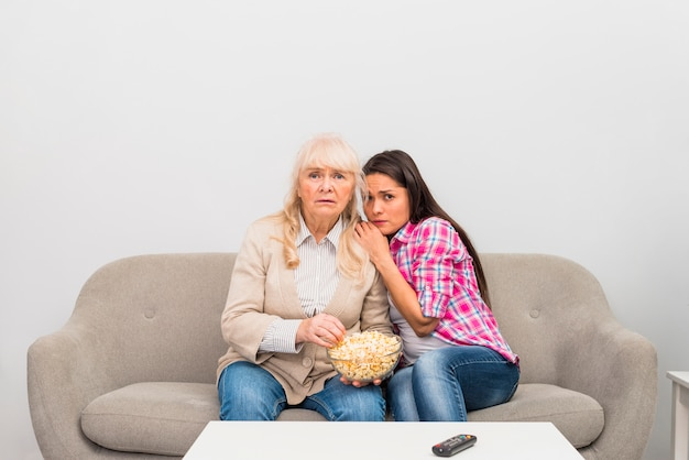 Young daughter watching horror movie with her senior mother holding popcorn bowl