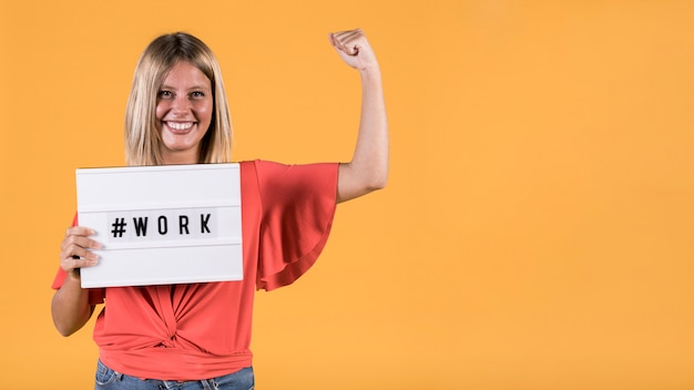 젊은 청각 장애인 여자 해시 태그 작업 텍스트와 함께 가벼운 상자를 들고 노란색 배경 위에 근육을 flexing