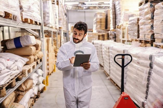 倉庫を歩き回り、タブレットを使用して商品の給与をチェックする、保護用の白い滅菌制服を着た若い熱心なひげを生やしたビジネスマン。コロナウイルス/ covid19発生の概念。
