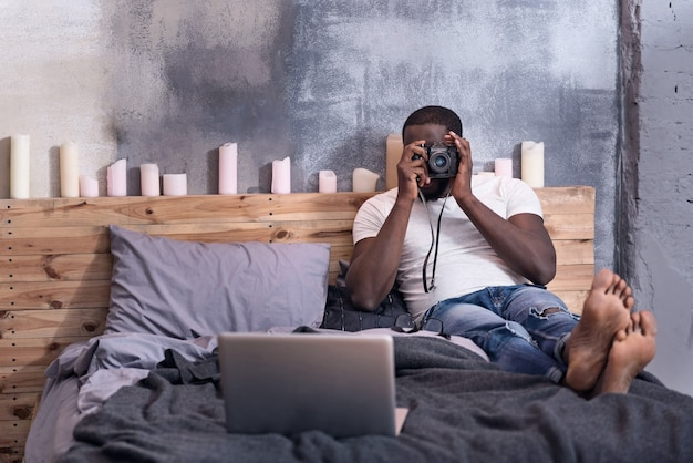 写真を作り、寝室に横たわっている間、カメラを持っている若い喜びの男。