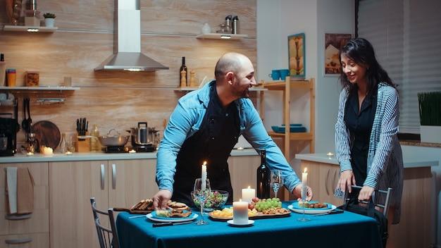 건강에 좋은 음식으로 축제 저녁 식사를 준비하는 젊은 남자, 직장에서 돌아온 여자가 남편에게 키스하고 포옹하는 것을 기뻐했습니다. 그의 아내를 위해 요리하는 남성, 부엌에서 기다리는 낭만적인 저녁 식사
