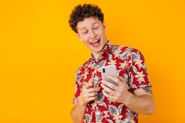 노란색에 고립 된 핸드폰을 사용 하 고 가리키는 젊은 기쁘게 남자