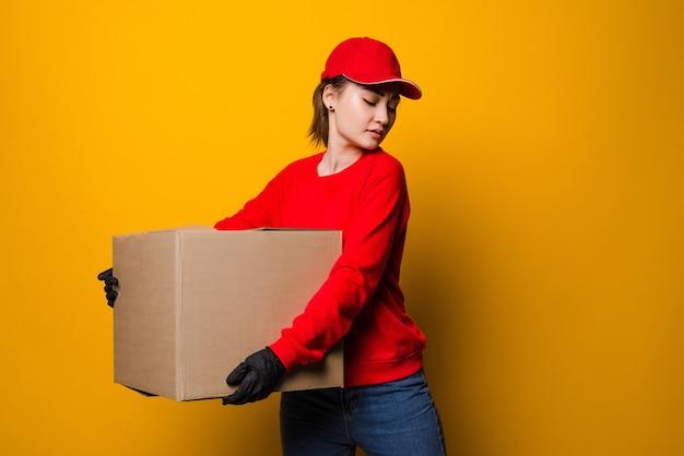 Молодая азиатская женщина доставки держит и несет картонную коробку, изолированную на желтом
