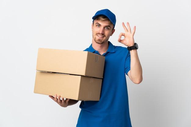 Молодой доставщик блондинки изолированы, показывая знак ок пальцами