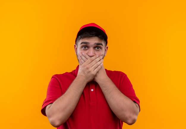 赤い制服とキャップの若い配達少年は手で口を覆ってショックを受けた