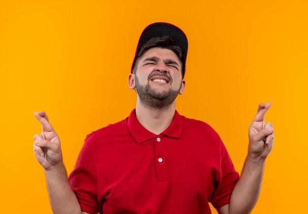Giovane ragazzo delle consegne in uniforme rossa e berretto con gli occhi chiusi, rendendo desiderabili le dita incrociate con espressione di speranza