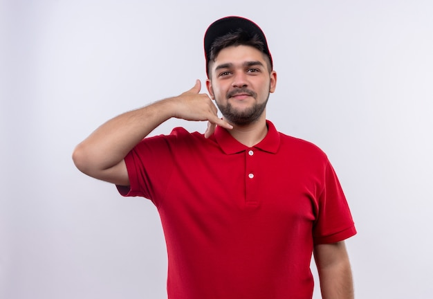Young delivery boy in red uniform and smiling confident making call me gesture