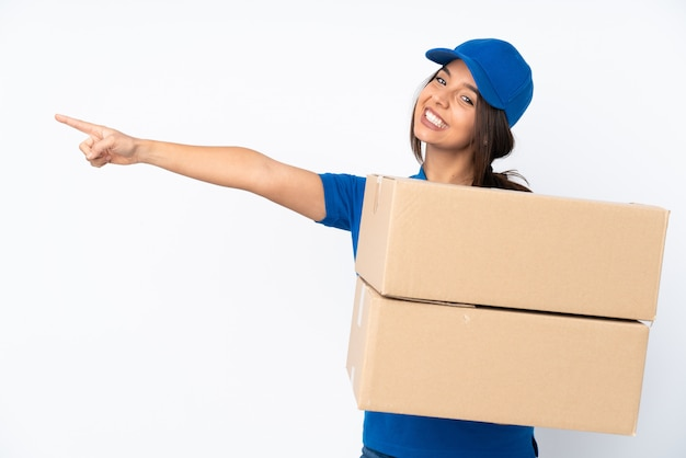 Young delivery brunette woman pointing finger to the side and presenting a product