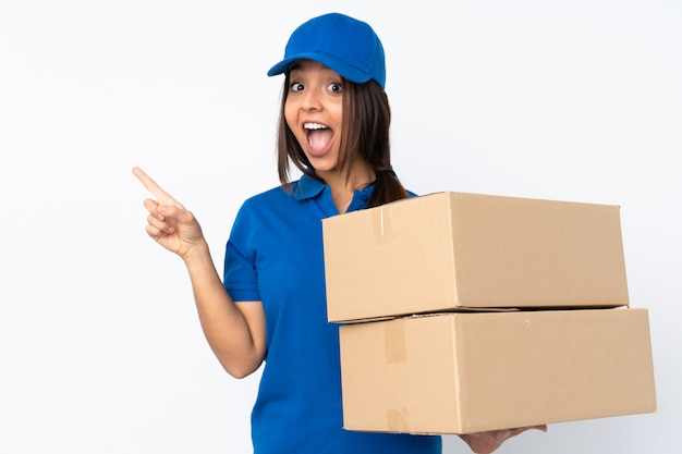Young delivery brunette woman surprised and pointing side