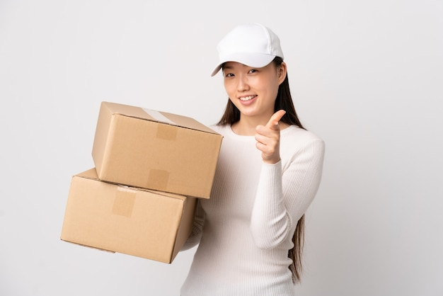 Young delivery chinese woman over isolated white wall points finger at you