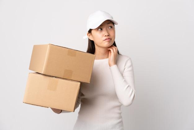 아이디어를 생각하는 고립 된 흰색 배경 위에 젊은 배달 중국 여자