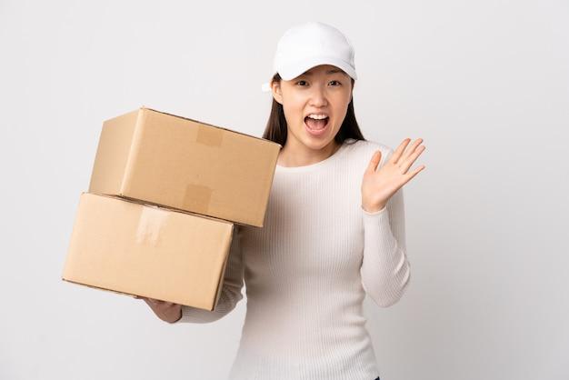 Молодая китаянка доставки по изолированной белой стене несчастна и разочарована чем-то