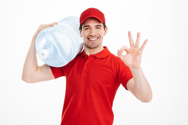 Молодой курьер доставки в красной форме транспортировки бутылку пресной воды и показывая большой палец ок знак, изолированных на пустое пространство