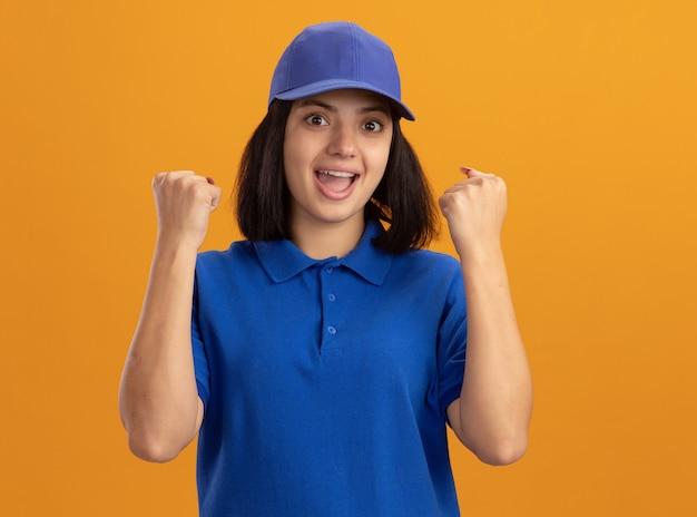 Giovane ragazza delle consegne in uniforme blu e berretto che stringe i pugni felice ed eccitato in piedi sopra la parete arancione