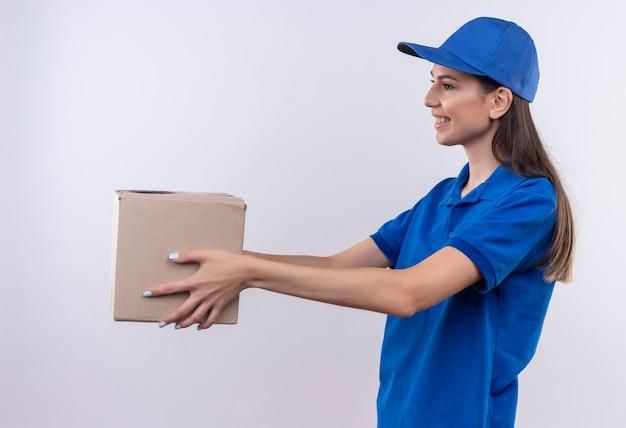 Giovane ragazza di consegna in uniforme blu e cappuccio che dà il pacchetto della scatola ad un cliente che sorride amichevole