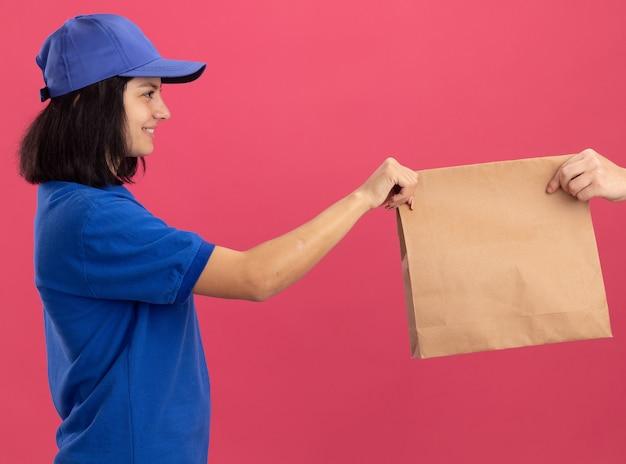 Giovane ragazza di consegna in uniforme blu e cappuccio che dà il pacchetto di carta a un cliente che sorride amichevole che sta sopra la parete rosa