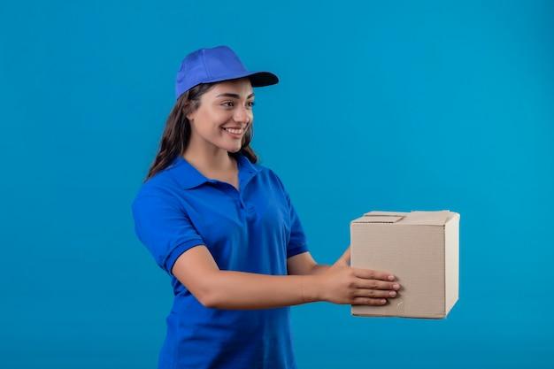 Giovane ragazza di consegna in uniforme blu e cappuccio che tiene il pacchetto della scatola dandolo a un cliente in piedi su sfondo blu