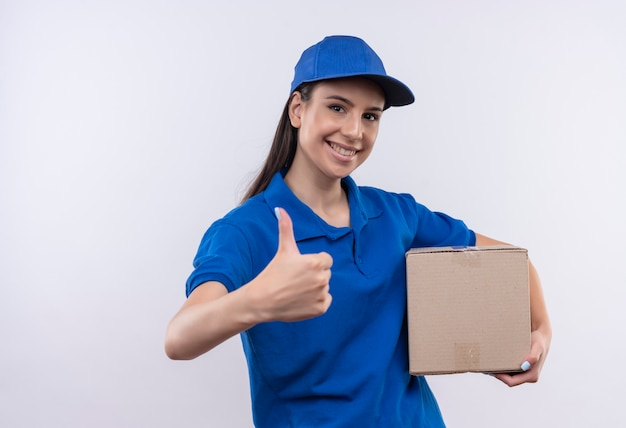 Young delivery girl in blue uniform and cap holding box package smiling confident showing thumbs up