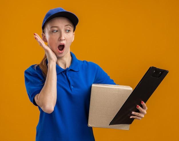 Giovane ragazza delle consegne in uniforme blu e cappuccio con scatola di cartone e appunti che sembra stupita e sorpresa in piedi sul muro arancione