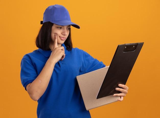 Giovane ragazza di consegna in uniforme blu e cappuccio che tiene scatola di cartone e appunti guardandolo con espressione confusa in piedi sopra la parete arancione