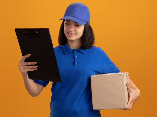 Young delivery girl in blue uniform and cap holding cardboard box and clipboard looking at it with smile on face standing over orange wall